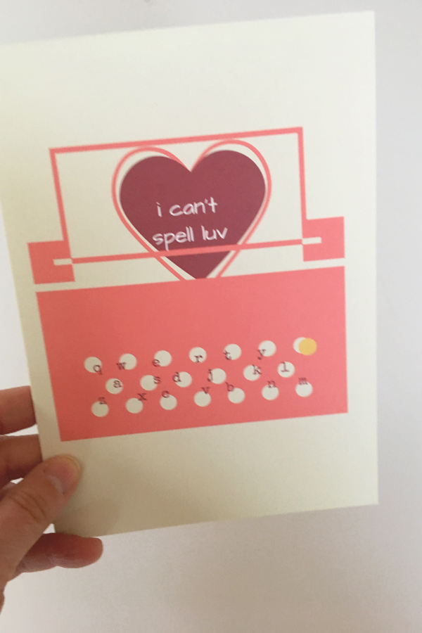 hand holding one of these funny love cards featuring pink typewriter and page being typed that reads I can't spell luv in dark red heart