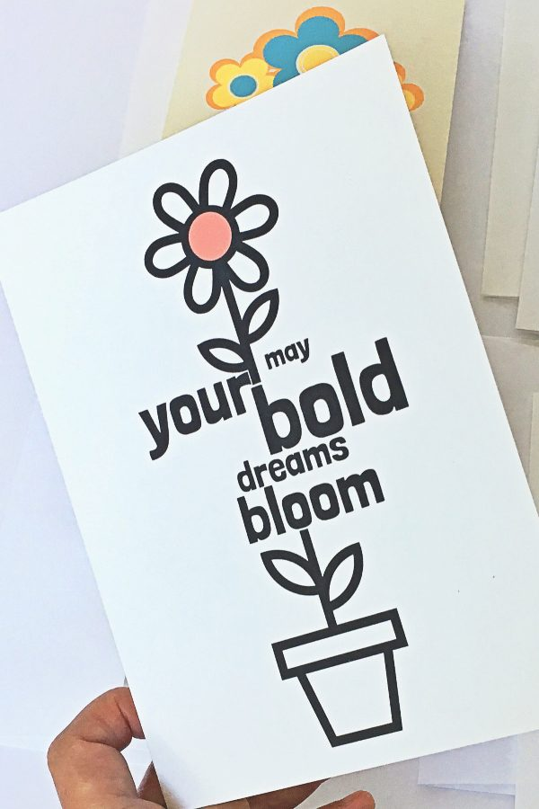 white greeting card with black illustration of flower growing out of flower pot and words may your bold dreams bloom positioned along the stem living coral red circle at center of flower