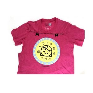 pink t-shirt embellished with blue seed glass beads, black cross stitch embroidery and felt ribbons with black graphic of smiling girl and various symbols on yellow circle with blue trim shows how T shirt from collection has been transformed into beaded embroidered t
