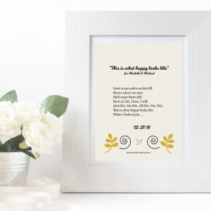 white frame with art print of lyrics to custom wedding song and pot of white flowers beside it